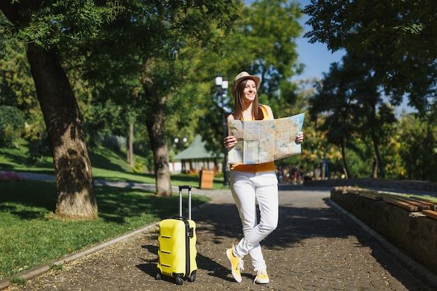 노란색 여름 캐주얼 옷을 입은 젊고 아름다운 여행자 관광 여성, 여행 가방 도시 지도가 있는 모자는 도시 야외에서 산책합니다. 주말 휴가를 여행하기 위해 해외로 여행하는 소녀. 관광 여행 라이프 스타일.