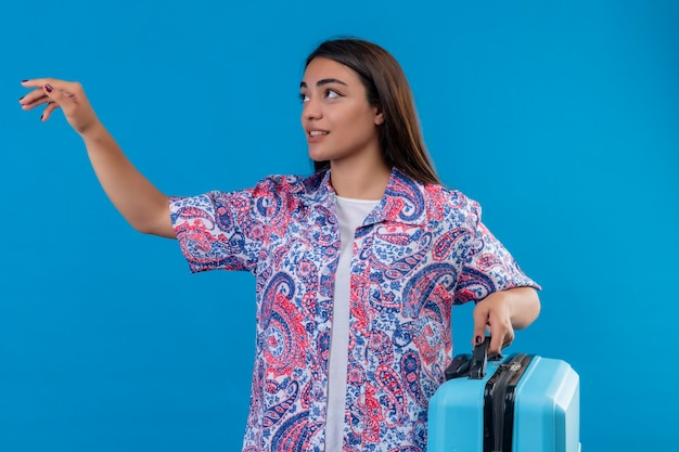 Young beautiful traveler woman holding blue suitcase looking aside gesturing with hand asking to come standing over blue background