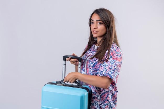 Giovane bella donna del viaggiatore che tiene la valigia blu che osserva da parte con espressione fiduciosa pronta a viaggiare in piedi su sfondo bianco