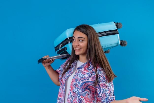Giovane bella donna del viaggiatore che tiene valigia blu che guarda da parte con il fronte felice che sorride allegramente sopra la parete blu