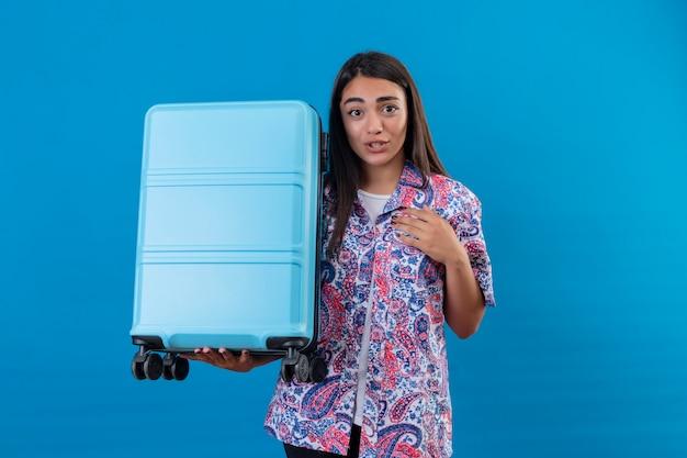 Молодая красивая женщина-путешественница, держащая синий чемодан, выглядит смущенной и удивленной, стоя на синем фоне