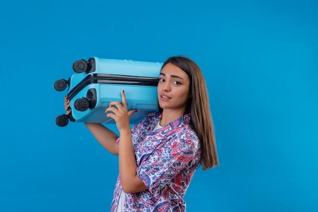Молодая красивая женщина-путешественница, держащая синий чемодан на плече, выглядит смущенной, стоя на синем фоне