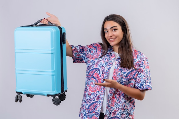 Молодая красивая женщина-путешественница, держащая синий чемодан, указывая рукой на нее, весело улыбаясь, стоя на белом фоне