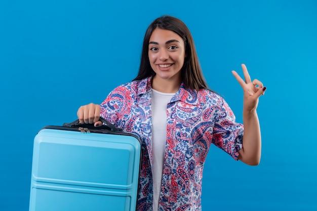 Donna giovane bella viaggiatore che tiene la valigia blu sorridente allegramente facendo segno di vittoria pronto a viaggiare in piedi su sfondo blu