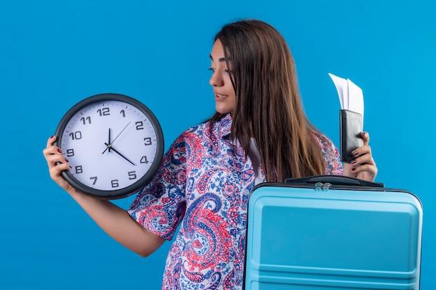 Молодая красивая женщина-путешественница держит синий чемодан с билетами и часами в руке, глядя на него, смущенно стоя на синем фоне