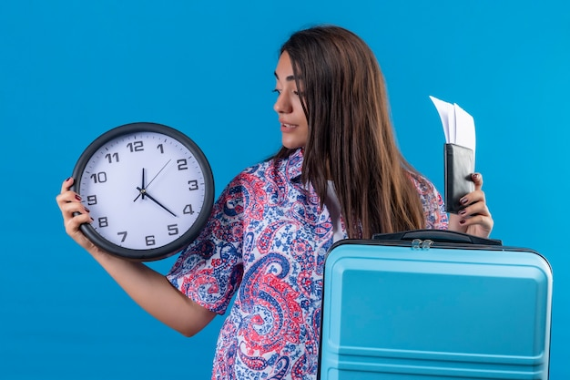 Young beautiful traveler woman holding blue suitcase with ticket tickets and clock in hand looking at it confused standing over blue background