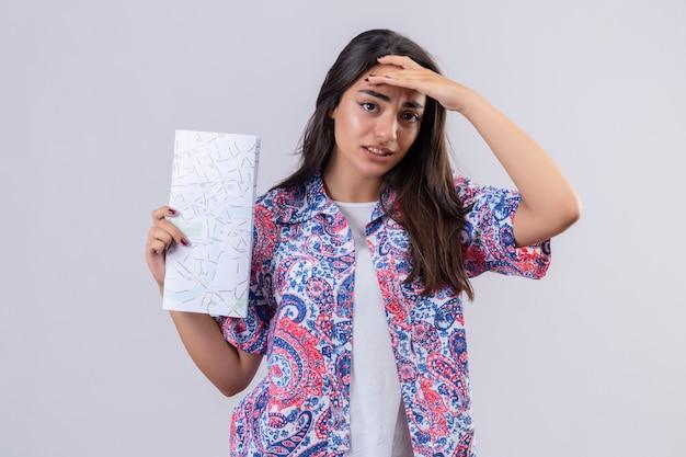白い背景の上に立っている地図を保持している混乱している感動的な頭の疑わしい表現立っている若い美しい旅行者女性