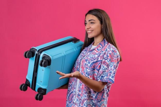 ピンクの背景の上に立って質問をする式で手で身振りで示す幸せそうな顔でよそ見スーツケースを保持している若い美しい旅行者女性