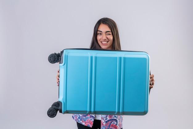 Молодая красивая путешественница женщина, держащая чемодан, глядя в камеру, подмигивая, весело улыбаясь, стоя на изолированном белом фоне