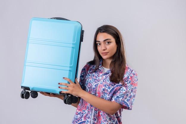 白い背景の上に立っている自信を持って式でカメラを見てスーツケースを持って若い美しい旅行者女性