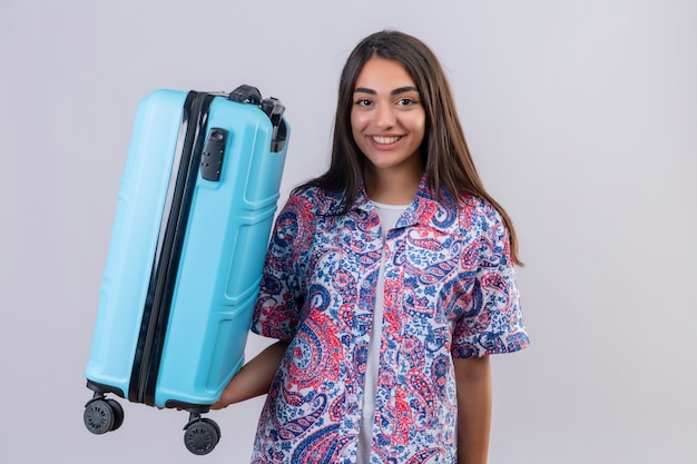 Young beautiful traveler woman holding suitcase looking confident, positive and happy, smiling cheerfully, ready to travel over white wall