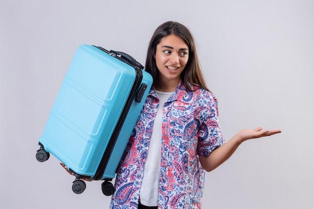 白い背景の上に立っている質問をするように手と式でジェスチャーを混乱しているスーツケースを持って若い美しい旅行者女性