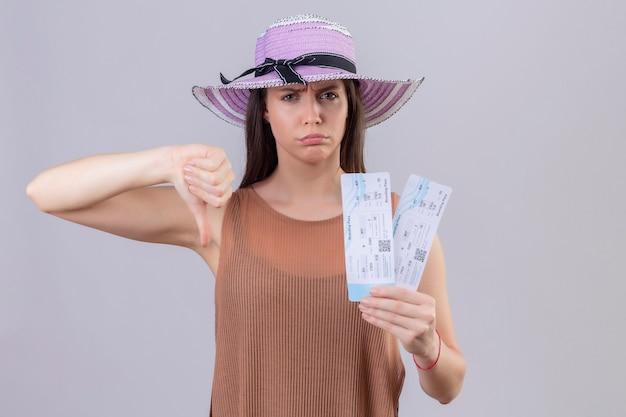 Молодая красивая женщина путешественника в летней шляпе держит авиабилеты, глядя в камеру с хмурым лицом, показывая пальцы вниз, стоя на белом фоне