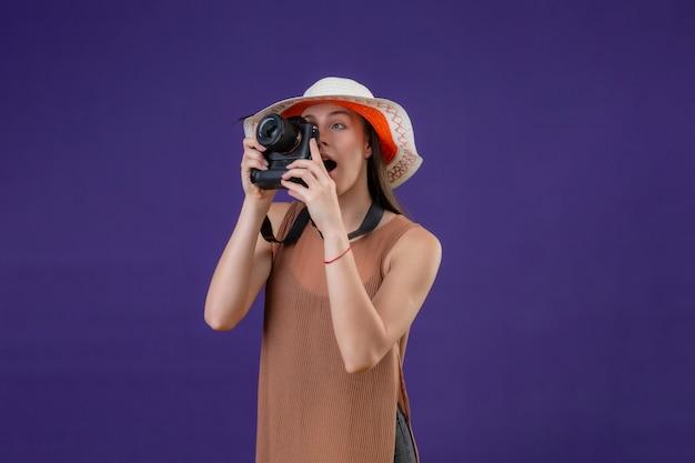 紫色の背景の上にカメラ立って写真を撮る夏帽子の若い美しい旅行者女性