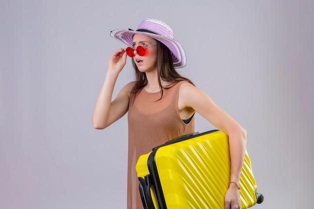 Молодая красивая женщина-путешественница в летней шляпе в красных солнцезащитных очках, держащая желтый чемодан, выглядит удивленной и разочарованной, стоя на белом фоне