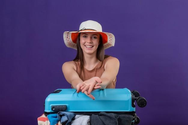 紫色の背景の上に立っている顔に笑顔でカメラを見て楽観的で幸せな服でいっぱいのスーツケースと夏帽子の若い美しい旅行者女性
