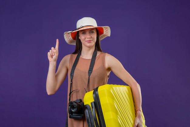 黄色のスーツケースとカメラ肯定的で幸せな笑みを浮かべて人差し指を紫色の背景の上に立って夏帽子の若い美しい旅行者女性