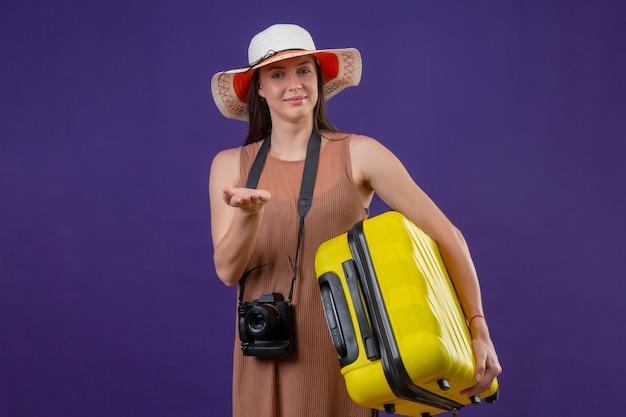 Молодая красивая женщина-путешественница в летней шляпе с желтым чемоданом и камерой позитивная и счастливая улыбка, указывая рукой на камеру, стоя на фиолетовом фоне