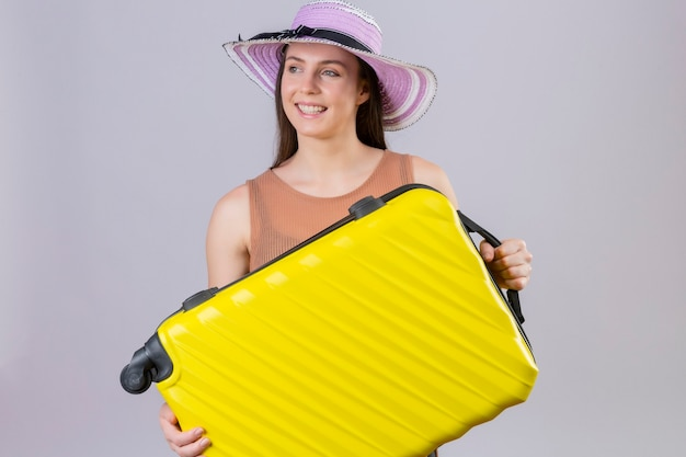 Young beautiful traveler woman in summer hat holding yellow suitcase smiling with happy face standing over white background