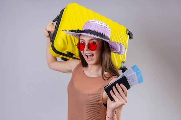 Young beautiful traveler woman in summer hat wearing red sunglasses holding yellow suitcase and air tickets smiling cheerfully with happy face over white wall