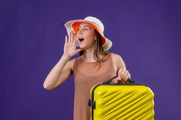 Young beautiful traveler woman in summer hat with yellow suitcase shouting or calling someone with hand near moth standing over purple background