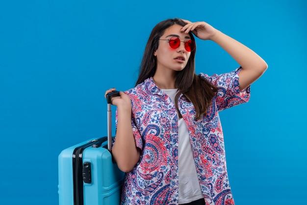 青い背景の上に立っている疑問を持つ物思いに沈んだ表情でよそ見青いスーツケースを持って赤いサングラスをかけている若い美しい旅行者女性