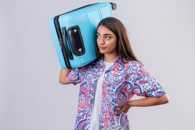 Young beautiful traveler woman with suitcase on shoulder displeased looking aside over isolated white wall