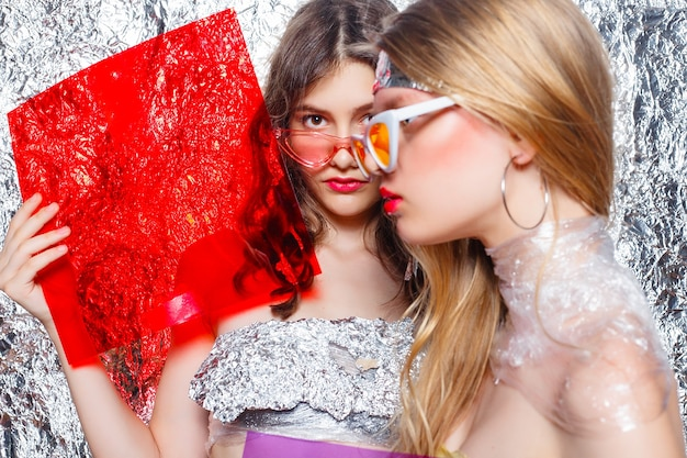 Молодые красивые две девушки друзья на серебряном фоне. введенная в моду художническая женщина с причудливым составом искусства. стиль vogue. креативность. модная девушка. женщина портрета красоты. красота лица с цветными фильтрами