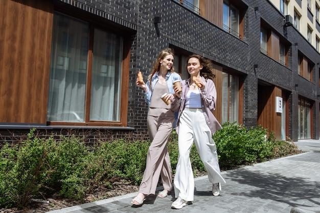 젊고 아름다운 두 여성은 도시 거리를 배경으로 함께 걷고, 소통하고, 커피를 마시고, 먹고, 함께 즐거운 시간을 보낸다