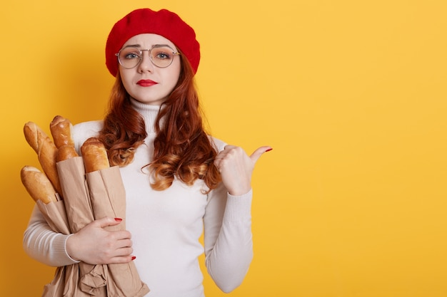 Young beautiful upset woman holding bag of fresh healthy bread on yellow