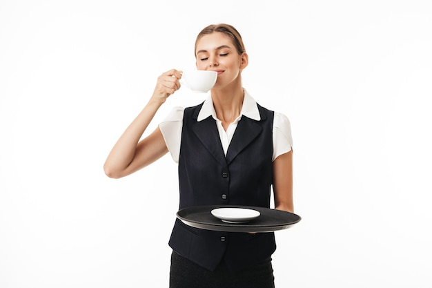 Young beautiful waitress in uniform holding tray while smelling fresh cup of coffee