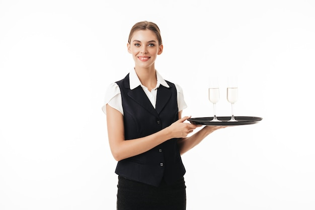 Young beautiful waitress in uniform holding tray with glasses while happily