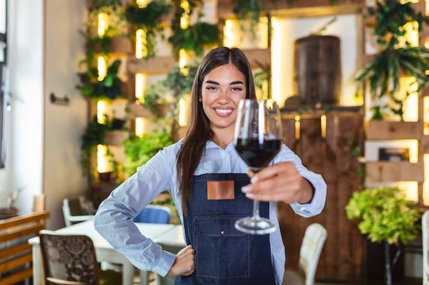 소박한 레스토랑에서 고객을 제공하는 한 손에 레드 와인 한 잔을 들고 앞치마를 입고 젊은 아름다운 웨이트리스. 레스토랑에서 소믈리에 추천 와인.