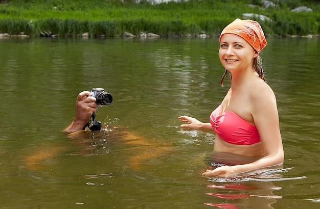 Молодая красивая мокрая женщина в купальнике стоит в реке, в то время как мужчина фотографирует с цифровой камерой с поверхности воды, экологический туризм.