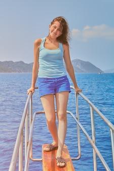 Молодая красивая белая женщина около 19 лет стоит на яхте и принимает солнечные ванны во время морского сезона.
