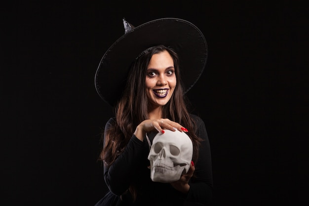 Young beautiful witch in a black dress doing witchcraft on a human skull. mysterious witch in a black dress for halloween.