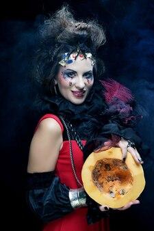 暗い背景の上にカボチャを持って明るいマルクと若い美しい魔女