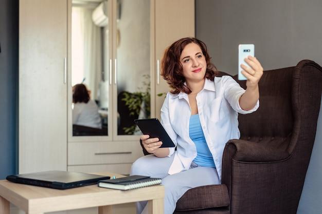 30歳の白いシャツを着た若い美しい女性が動作し、ホームオフィスの椅子に座って、ビデオ通話を使用して顧客と問題を話し合っている