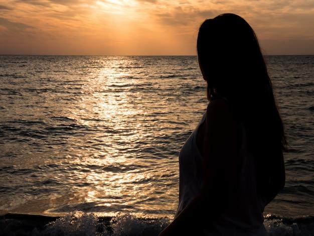 海に沈む夕日を眺める若い美女。自然と再会した美女