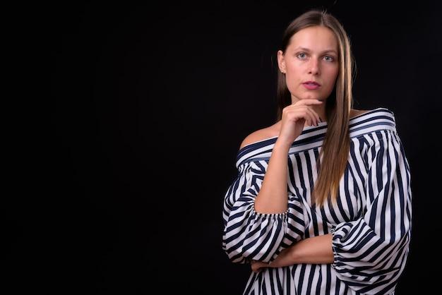 黒い空間に対して若い美しい女性