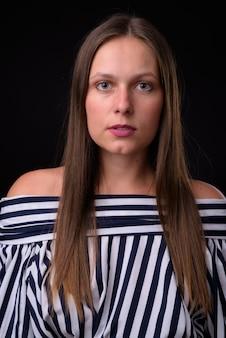 黒い壁に対して若い美しい女性