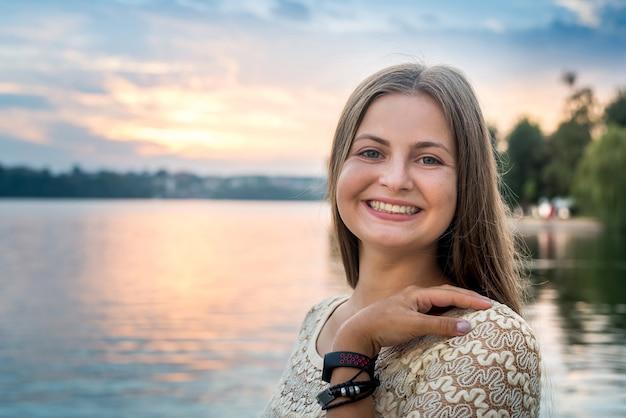 湖に沈む夕日に対して若い美しい女性