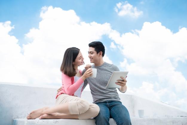 Молодая красивая женщина и азиатский мужчина смеются против темно-синего неба с облаками