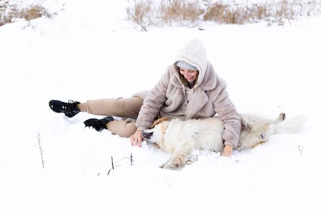 Молодая красивая женщина и ее золотистый ретривер веселятся зимой