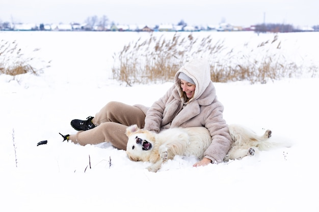 若い美しい女性と冬に楽しんでいる彼女のゴールデンレトリバー犬