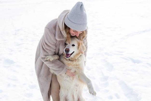 젊고 아름다운 여성과 그녀의 골든 리트리버 개가 겨울에 즐거운 시간을 보내고 있습니다.