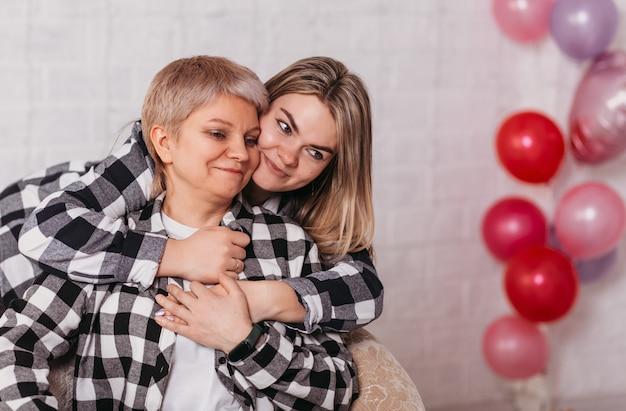 若い美しい女性と彼女のお母さんは風船のある部屋に寄り添う