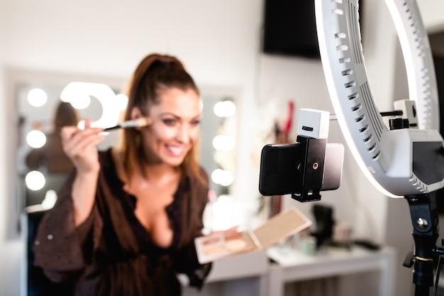 젊고 아름다운 여성과 전문적인 미인은 아티스트 블로거나 블로거가 메이크업 튜토리얼을 녹음하여 웹사이트나 소셜 미디어에서 공유합니다.