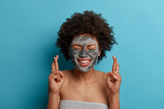 Young beautiful woman applies clay nourishng mask on face, smiles broadly, stands wrapped in towel, crosses fingers, awaits dreams come true, stands indoor. wellness, health care and beauty concept