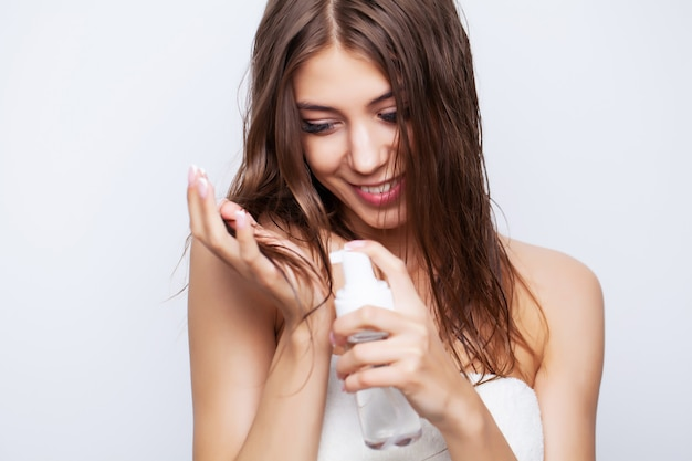 Young beautiful woman applies conditioner on damaged hair to restore and care for hair